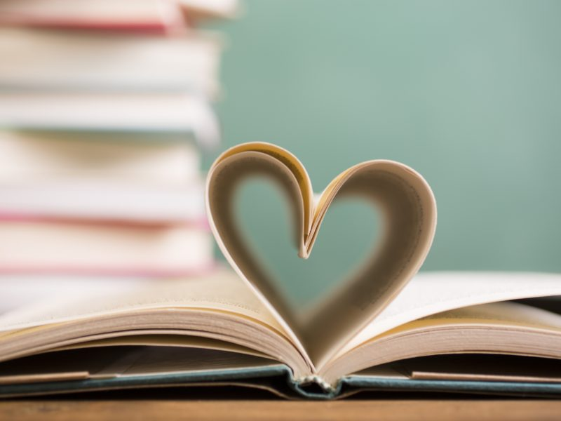 I love to read!  A heart shape created with open hardback book pages in foreground with a large stack of books and green chalkboard in background.  School classroom or library setting.  Education themes.   No people.